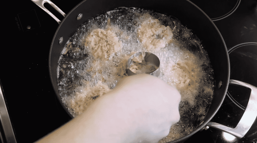 Adding latkes to frying pan