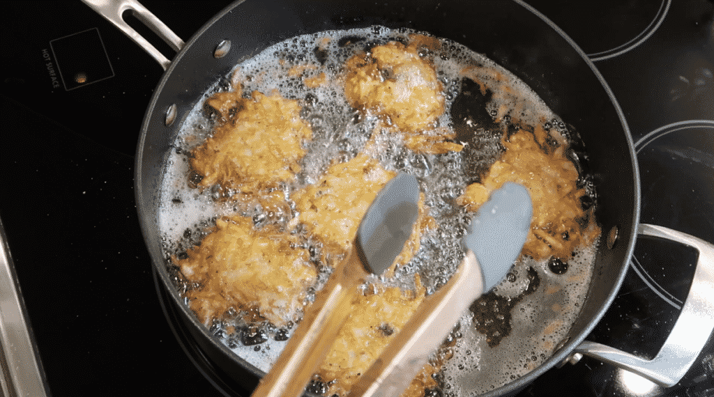 Latkes about to be removed from pan with tongs