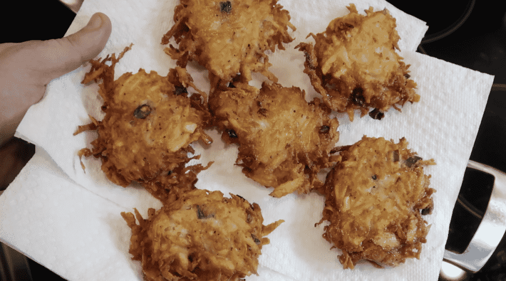 Placing fried latkes on a paper towel-lined plate.