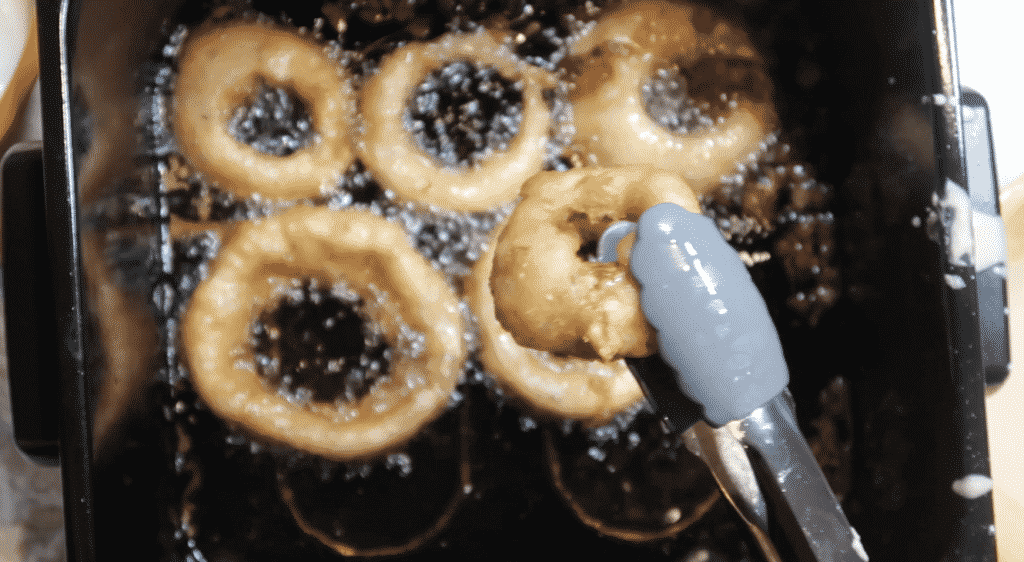 Frying onion rings and showing golden-brown color.