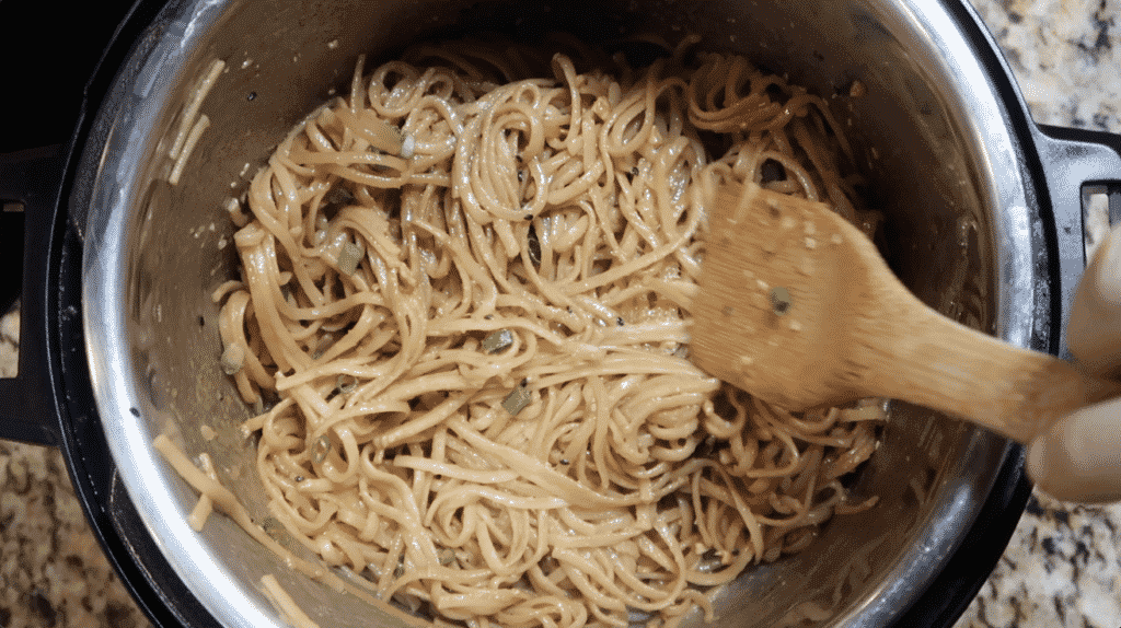 Tossing pasta with ingredients in the pot