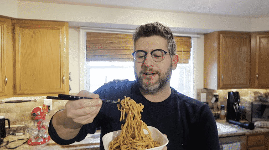 Man grabbing noodles with chopsticks