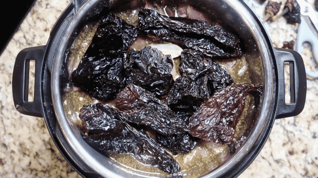 Laying chiles on top of pork in pot and pressure cooking.