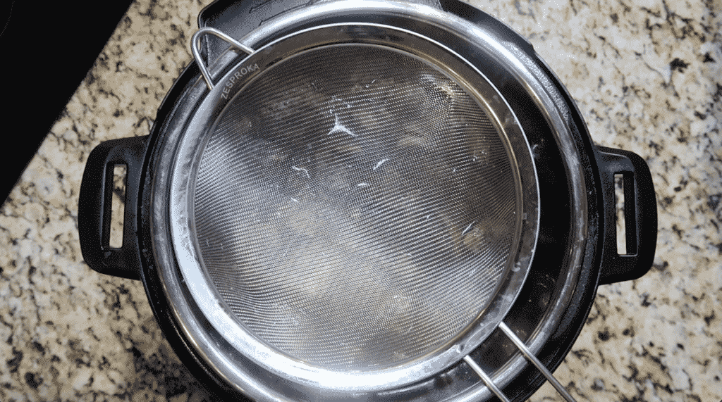 placing a fine-mesh strainer over the pot