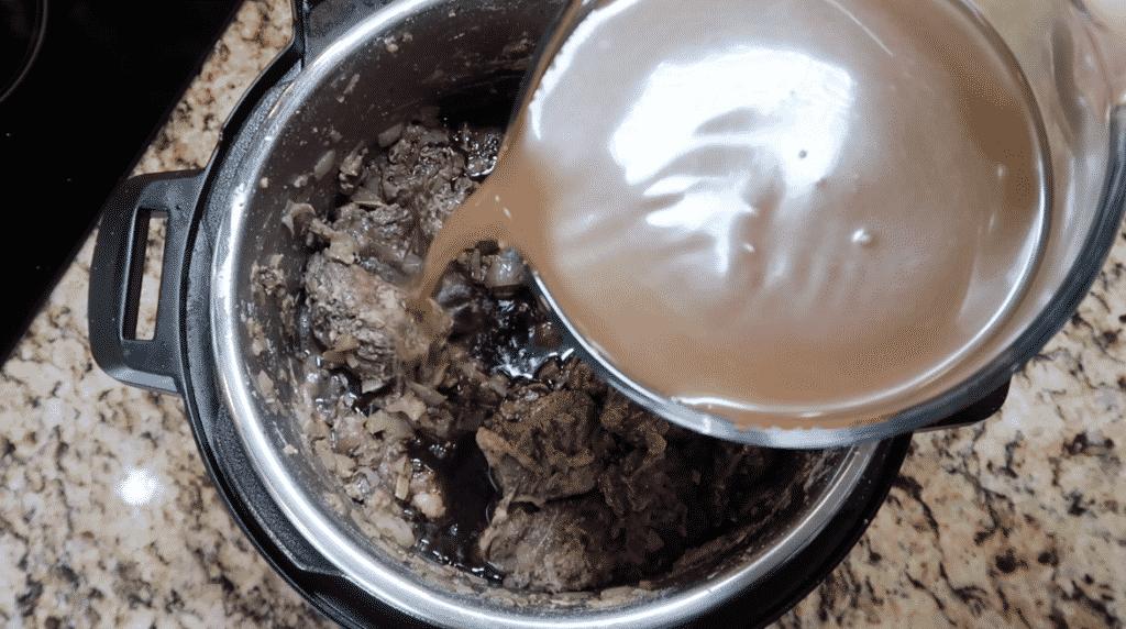 Adding beef broth to pot