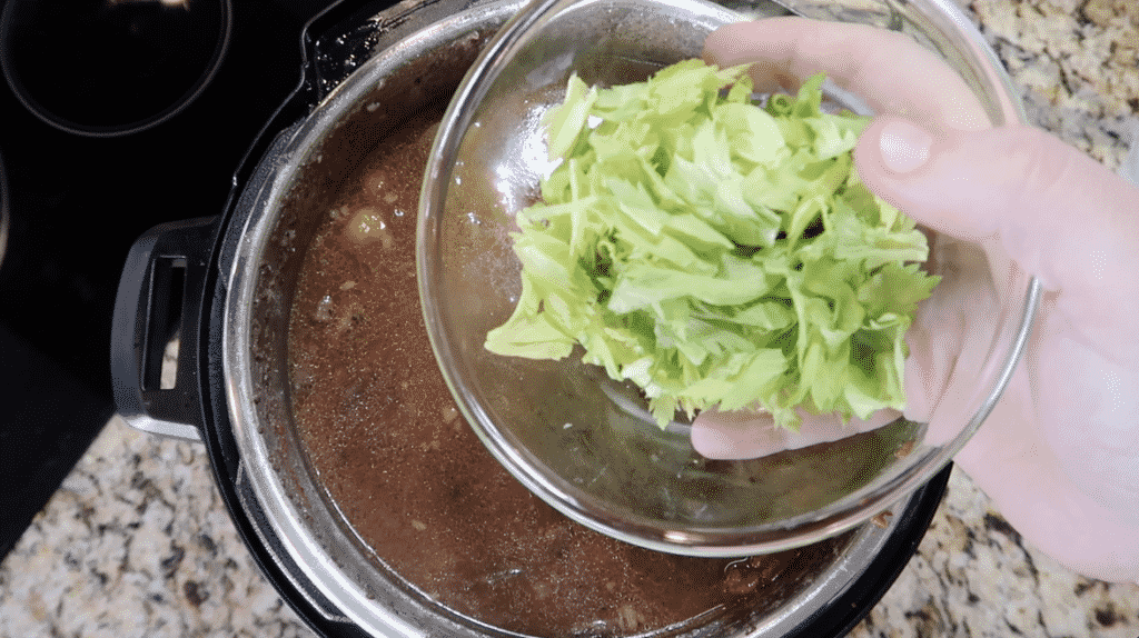 Adding celery leaves to stew