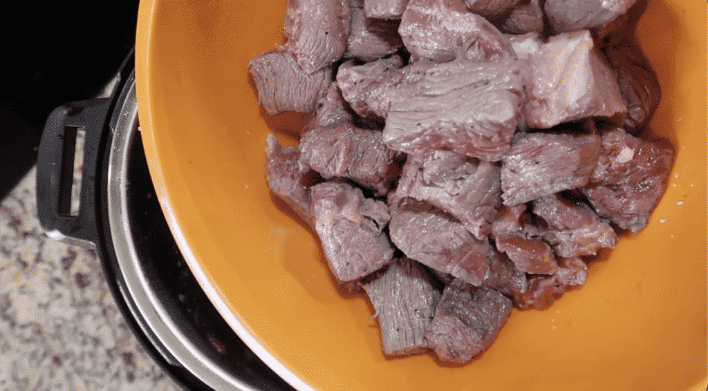 Adding seared meat to the pot