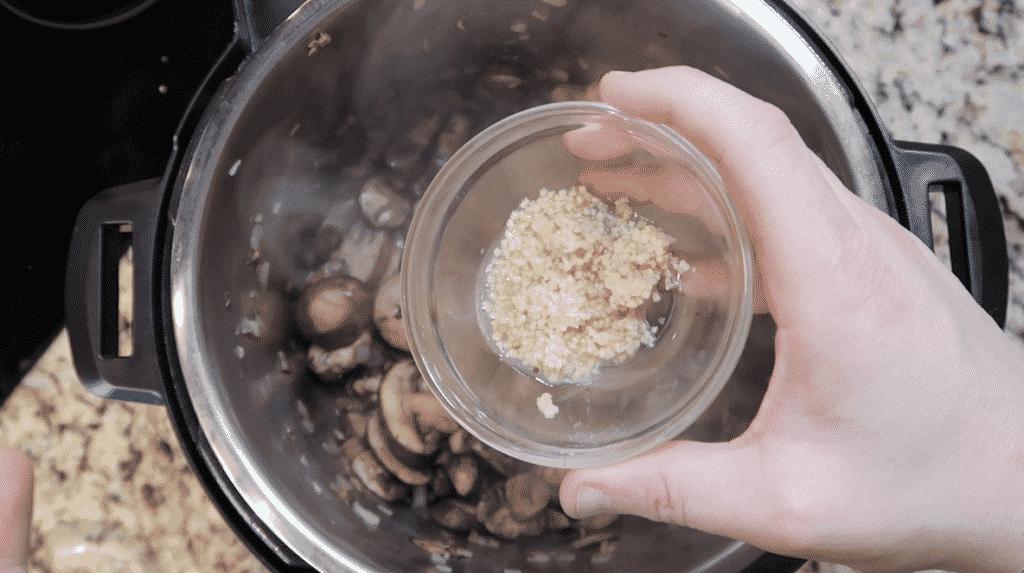Adding garlic to the pot.