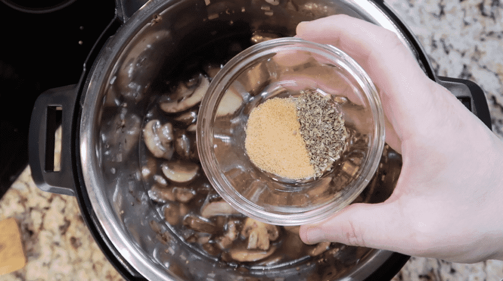 adding seasoned salt and oregano to the pot