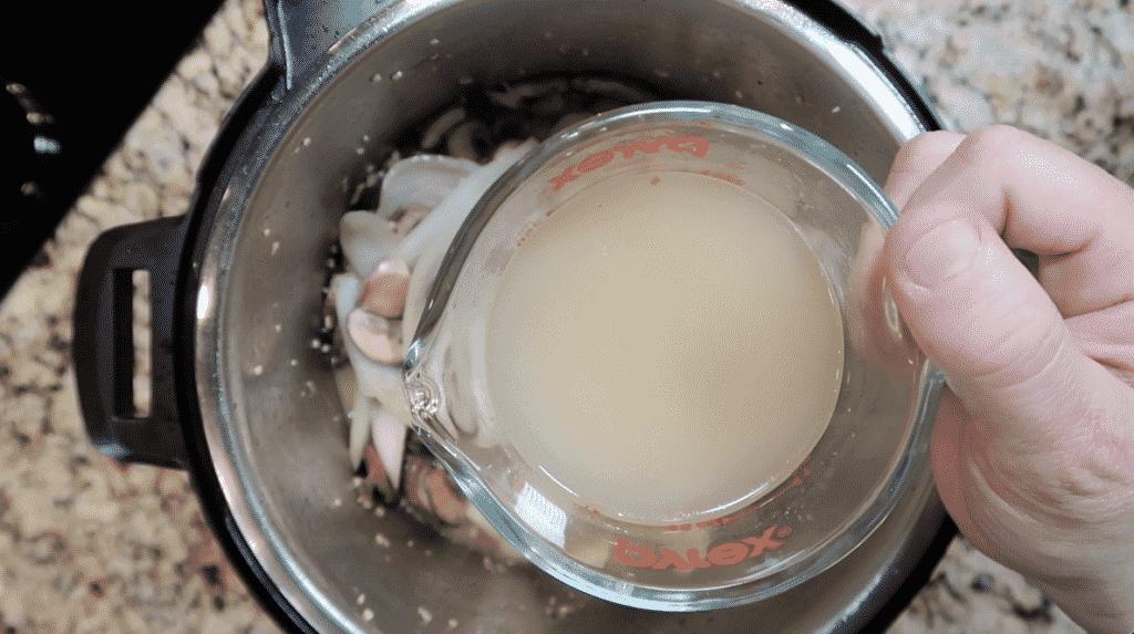 Adding broth to pot