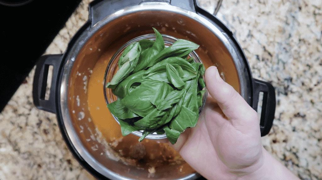 Adding fresh basil leaves