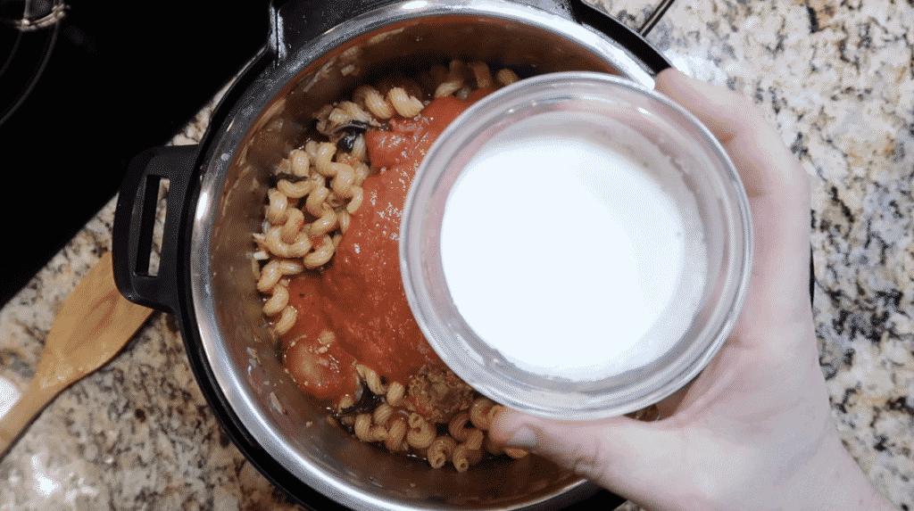 Adding heavy cream to pot.