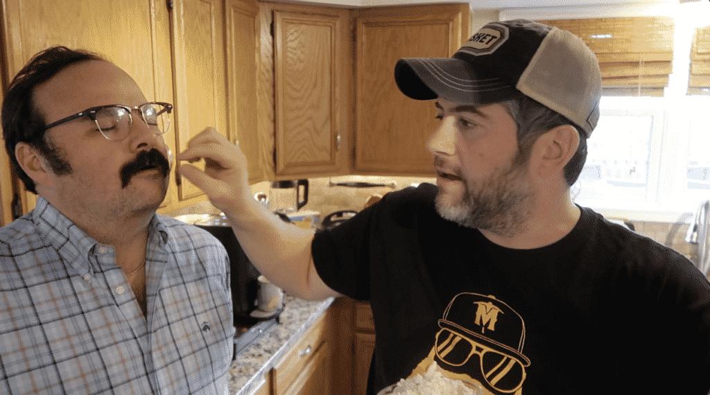 Man feeding man in blind taste test fashion